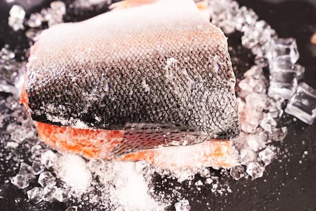 Lachs auf einem schwarzen steinbrett mit eiswürfeln.