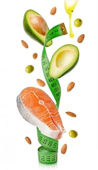 Lachs, avocado, mandeln, oliven und öl fliegen um maßband