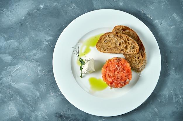 Lachs-avocado-tartar, croutons in einer weißen platte auf beton