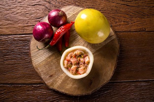 Lachs-ceviche mit passionsfruchtsauce auf hölzernem hintergrund