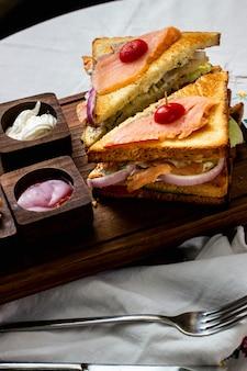 Lachs-club-sandwich mit gurken-salat mit roten zwiebeln