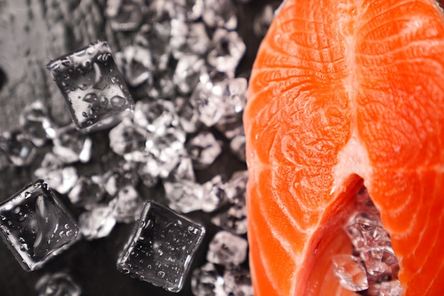 Lachs in stücke geschnitten auf einem schwarzen steinbrett mit eiswürfeln. roter fisch. frische forelle zum kochen.