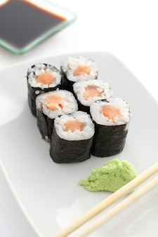 Lachs-maki-sushi mit stäbchen und sojasauce in weiß