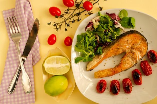 Lachs mit gerösteten kirschtomaten und gemischtem blattsalat und zitronenhälften. mediterranes essen. ansicht von oben
