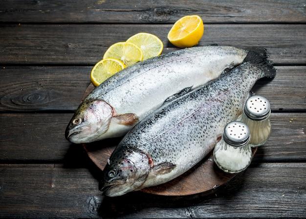 Lachs roher fisch auf einem schneidebrett mit zitrone. auf einem hölzernen hintergrund.