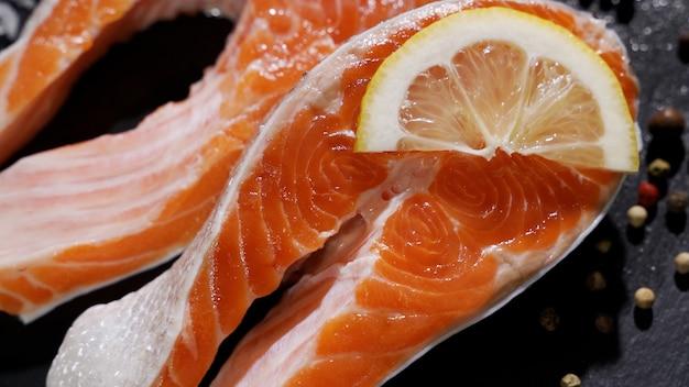 Lachs rohes forellen-rotfischsteak mit kräutern und zitrone und olivenöl auf schiefer gedreht