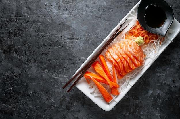 Lachs sashimi und imitat krabbe stick im japanischen stil mit kimchi, wasabi.