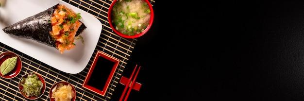 Lachs temaki sushi auf weißem teller in schwarzem hintergrund.