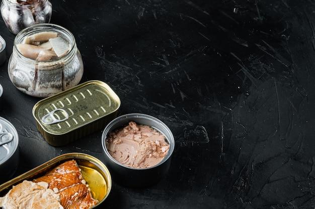 Lachs, thunfisch, forellenmakrele und sardelle - fischkonserven in blechdosen auf schwarz