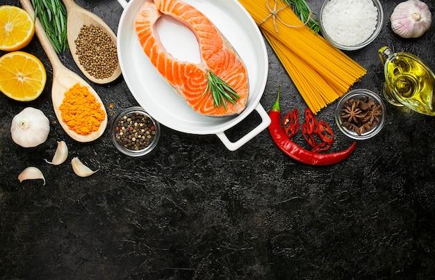 Lachsfilet mit aromatischen kräutern, gewürzen und gemüse auf dunklem hintergrund. kochkonzept. kulinarische hintergründe. lebensmittel hintergrund. gesunde lebensmittelbalance. tabellenhintergrundmenü. platz kopieren.