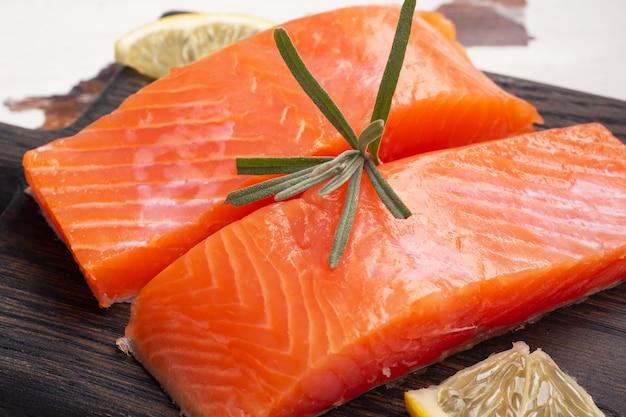 Lachsfilet, roter gesalzener fisch auf einem hölzernen schneidebrett. zitrone, rosmaringewürze.