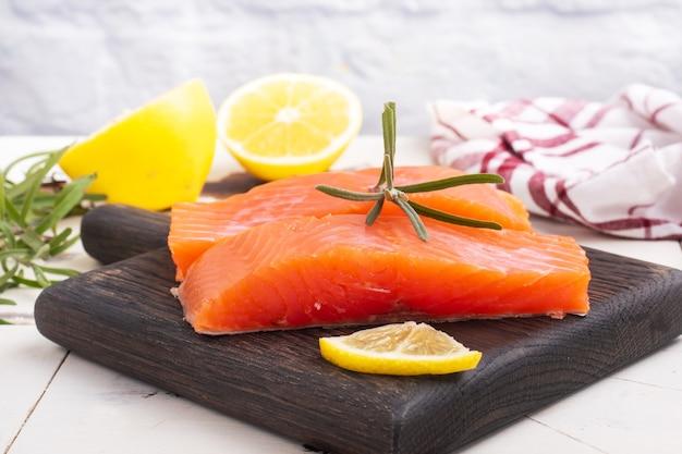Lachsfilet, roter gesalzener fisch auf einem schneidebrett aus holz. zitrone, rosmarin gewürze. platz kopieren.
