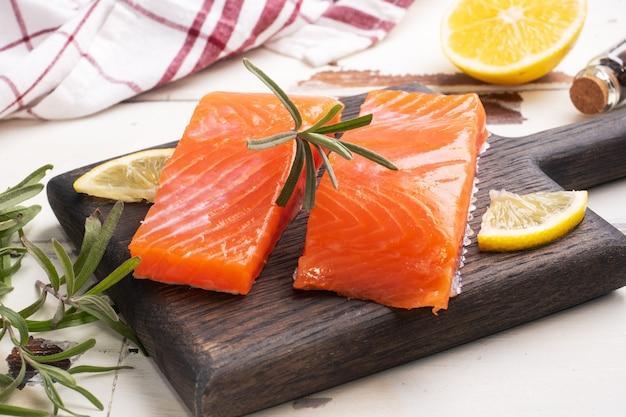 Lachsfilet, roter gesalzener fisch auf einem schneidebrett aus holz. zitrone, rosmarin gewürze.