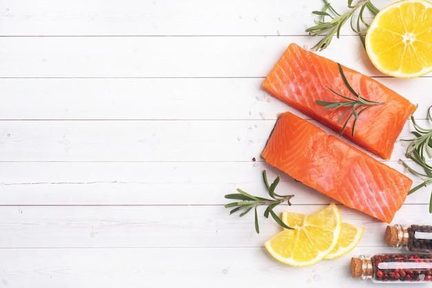 Lachsfilet, roter gesalzener fisch auf einem weißen tisch. zitrone, rosmaringewürze. speicherplatz kopieren.
