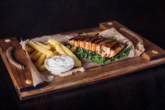 Lachsfiletsteak mit pommes frites auf einem holztablett, schöne portion, dunkler hintergrund.