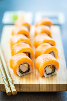 Lachsfischfleisch-sushirolle maki auf hölzerner platte