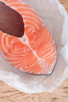 Lachsfischsteak auf hölzernem hintergrund. roter fisch auf papier