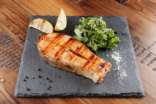 Lachsfischsteak mit zitrone und gemüse auf einer schieferoberfläche. hölzerner hintergrund