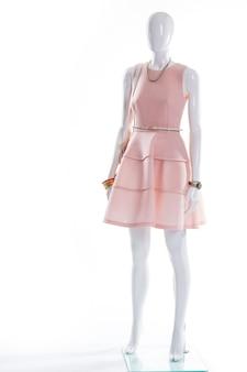 Lachskleid auf weißer schaufensterpuppe. abendkleid der dame auf schaufensterpuppe. kleid mit gürtel und uhr. kleid und accessoires mit u-ausschnitt.