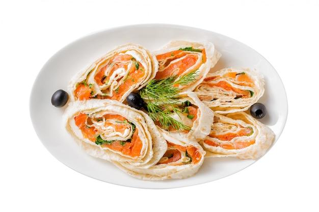 Lachslavasch rollt mit dill, käse und schwarzen oliven auf der weißen platte, die auf weißem hintergrund lokalisiert wird.