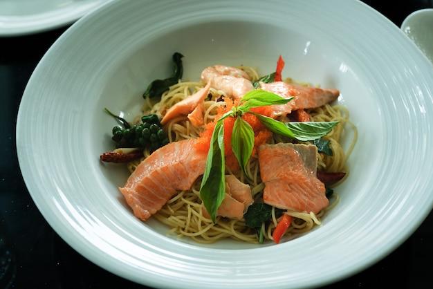 Lachspaghetti, geräucherter lachs und garnelenei mit würzigem thailändischem kraut. hausgemachtes essen.