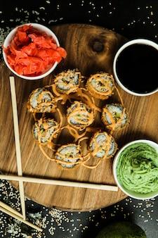 Lachsrolle mit reis, sojasauce, sesam, ingwer und wasabi