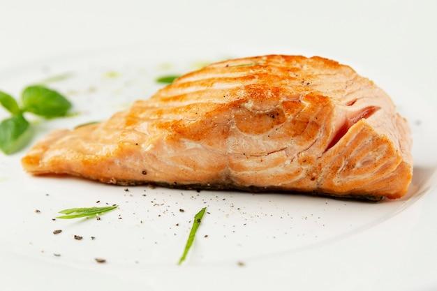 Lachsrotes fischsteak auf einem teller. leckeres mediterranes essen. seitenansicht. nahaufnahme. weißer hintergrund.