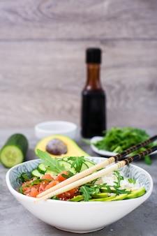 Lachssack mit avocado, rucola und gurke in einer schüssel und in essstäbchen