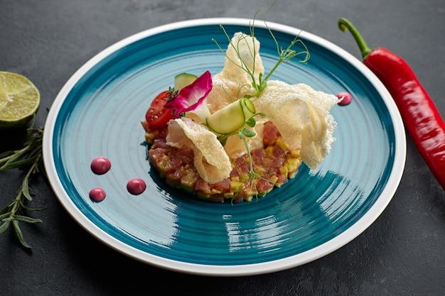 Lachssalat mit avocado, auf einem blau gestreiften teller, mit limette, mit chilischoten, essbaren blumen, rosmarin und pommes