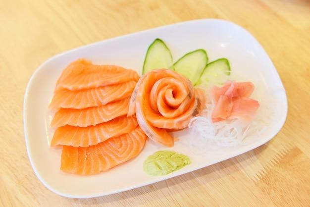 Lachssashimimenü stellte frische bestandteile der japanischen küche auf platte - rohes sashimilachsfilet des japanischen lebensmittels mit gemüsegurke und wasabi im restaurant ein