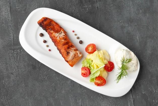 Lachssteak mit frischem gemüse und tzatziki-sauce. auf einem weißen teller. sicht von oben. auf grauem betonhintergrund.