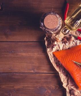 Lachssteak mit kräutern auf hölzernem hintergrund mit raum für text. im stil des instagram-filters.