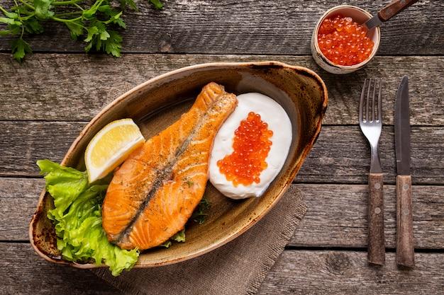 Lachssteakcreme und roter kaviar serviert mit messer und gabel. ansicht von oben