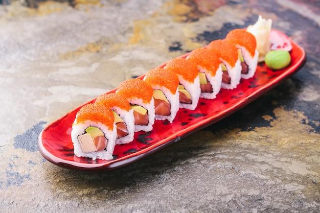 Lachssushi-rollen auf rotem teller alaska-rollen