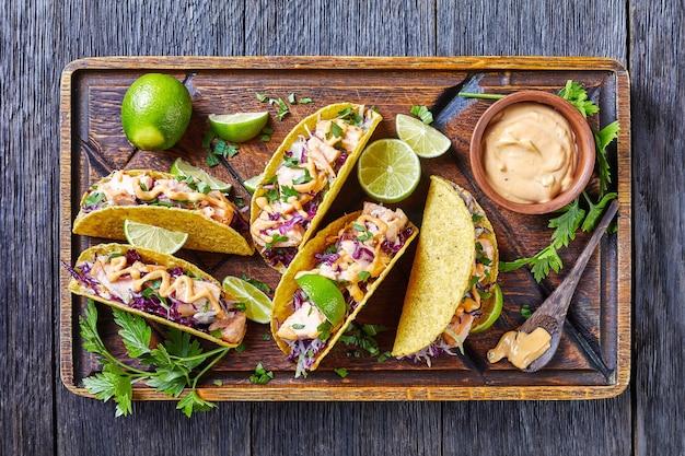 Lachstacos mit rotkohlsalat mit würziger joghurtsauce, bestreut mit fein gehackter petersilie, serviert auf einem groben schneidebrett auf einem dunklen holztisch, horizontale ansicht von oben, flach
