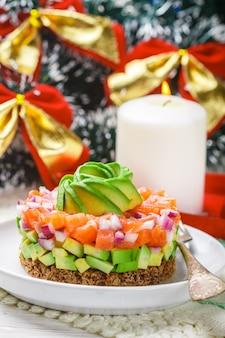 Lachstatar (forelle) mit avocado und roter zwiebel auf roggenbrot. vorspeise für weihnachten und neujahr