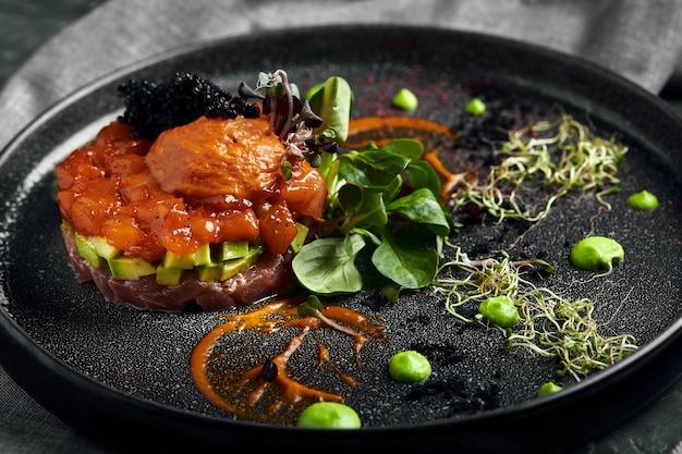 Lachstatar mit avocado auf einem dunklen teller, traditionelle italienische küche, gericht auf einer dunklen oberfläche, zurückhaltend mit kopierraum
