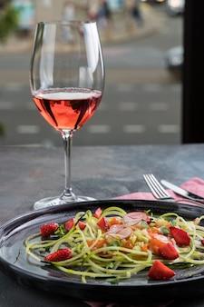 Lachstatar mit frischen erdbeeren und zucchinispaghetti. rustikaler hölzerner hintergrund, graue tischdecke und ein glas rotwein. ansicht von oben