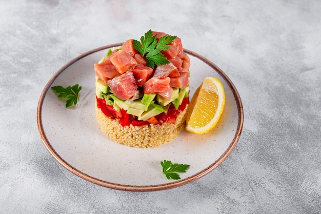 Lachstatar mit tomaten, avocado und quinoa auf einem teller
