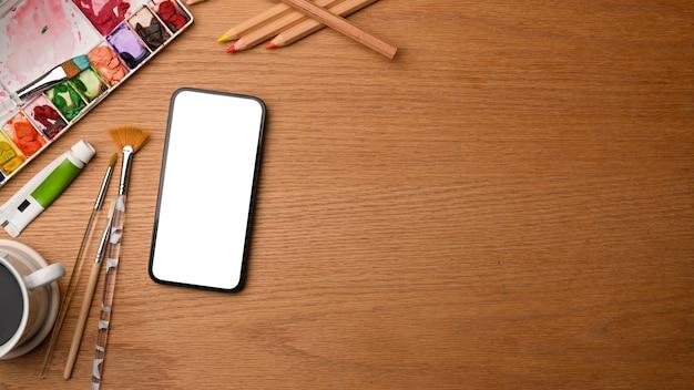 Lackierarbeitsplatz smartphone-modell und malerei liefert kopienraum auf der draufsicht des holzarbeitstisches