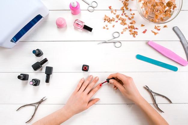 Lackiere deine eigenen nägel. maniküre-set und nagellack auf holzuntergrund. ansicht von oben. platz kopieren. stillleben. nagelpflege.