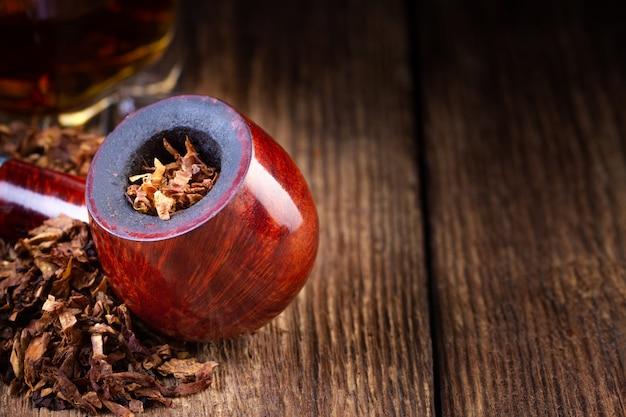 Lackierte pfeife und tabakhaufen auf vintage holztisch.