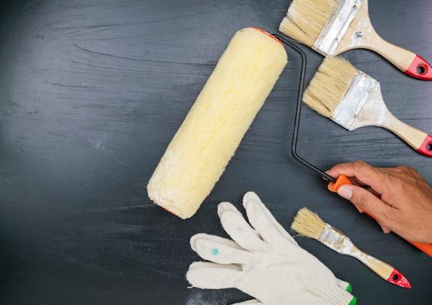Lackpinsel und weißer handschuh auf schwarzem hintergrund