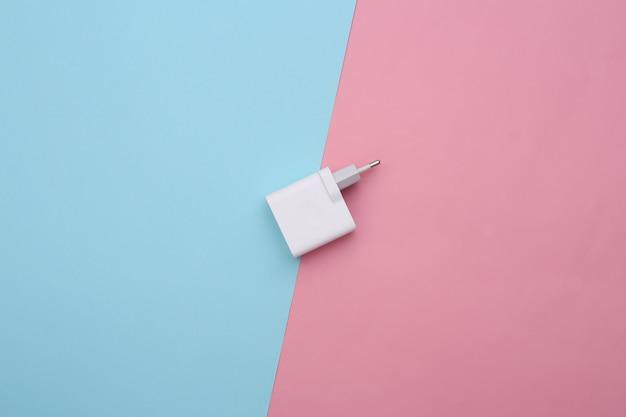Ladegerät-adapter auf einem blau-rosa pastellfarbenen hintergrund.