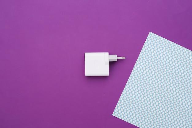 Ladegerät-adapter auf lila blauem hintergrund.