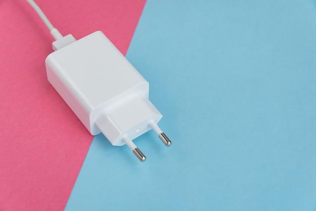 Ladegerät und usb-kabel typ c über rosa und blauem hintergrund