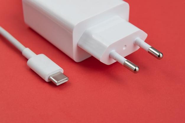 Ladegerät und usb-kabel typ c über rotem hintergrund
