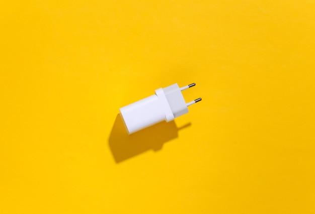 Ladegerätadapter auf gelbem hellem hintergrund mit tiefem schatten.