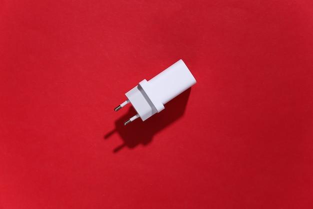 Ladegerätadapter auf rotem hellem hintergrund mit tiefem schatten.