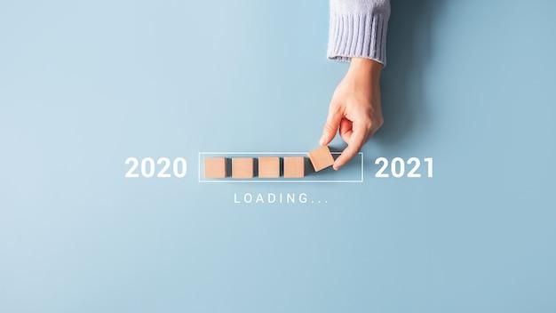 Laden des neuen jahres 2020 bis 2021 mit der hand, die den holzwürfel in den fortschrittsbalken legt.